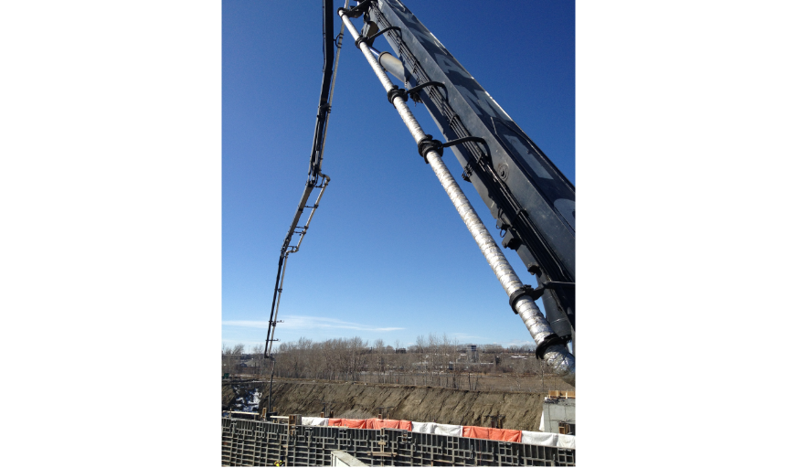 Dynamic Concrete Pumping boom pump reaching to pump concrete on the Trans-Canada, Canmore job