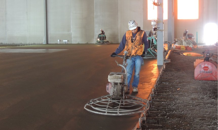 concrete finisher using a piece of concrete finishing equipment to complete a Dynamic Concrete Pumping project