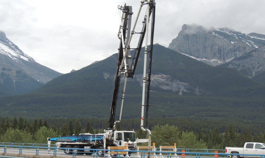 Dynamic Concrete Pumping boom pump being used on the Trans-Canada, Canmore project in front of snowy mountains