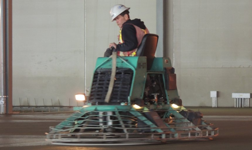 Dynamic Concrete Pumping concrete finisher on a piece of equipment and finishing a concrete job