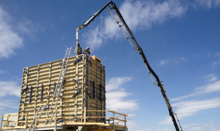 two Dynamic Concrete Pumping contractors guiding a concrete boom pump at a project
