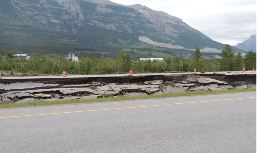 broken street after Southern Alberta flood washed out bridges and structures