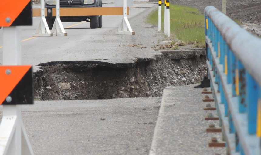 road washed away by flood in Southern Alberta
