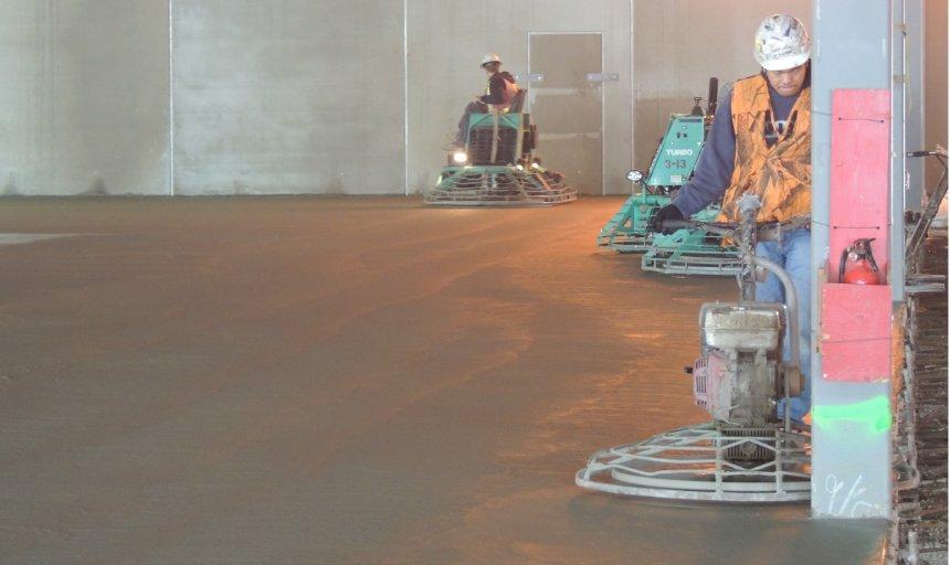 2 Dynamic Concrete Pumping employees finishing a job using concrete finishing equipment