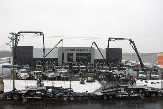 Dynamic Concrete Pumping equipment fleet in front of building