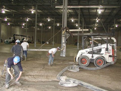 four Dynamic Concrete Pumping contractors using a Bobcat concrete placer to complete a project