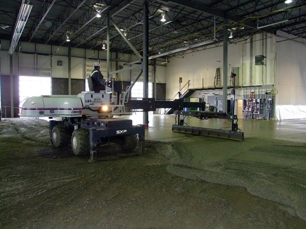 concrete contractor evenly placing concrete with laser screed equipment