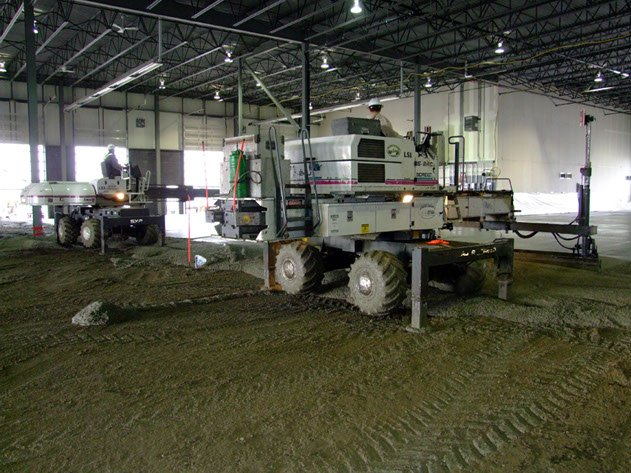 two pieces of Dynamic Concrete Pumping laser screed equipment leveling out a large concrete floor