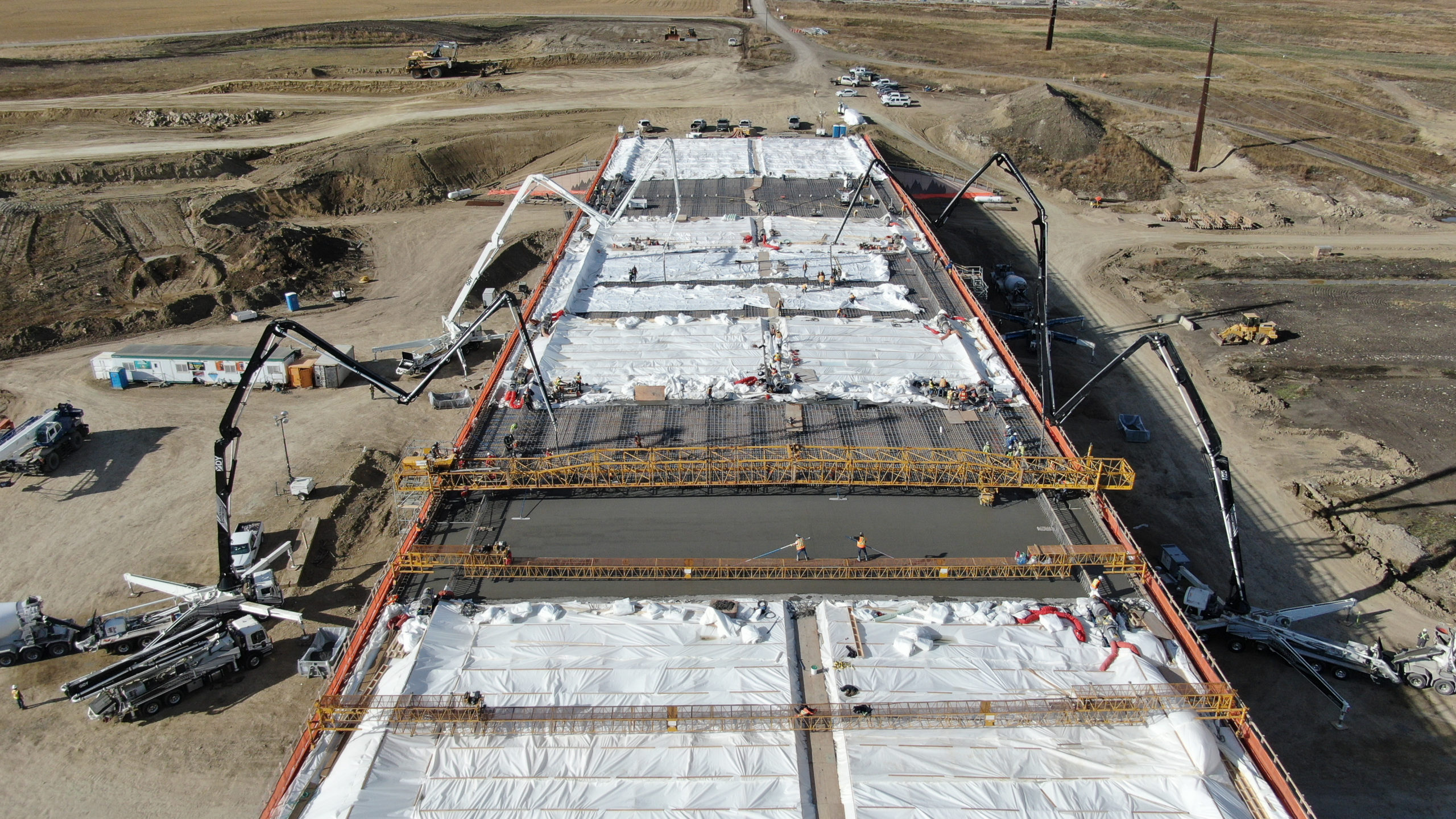 concrete boom pumps adding concrete to a structure at the SW Calgary Ring Road job