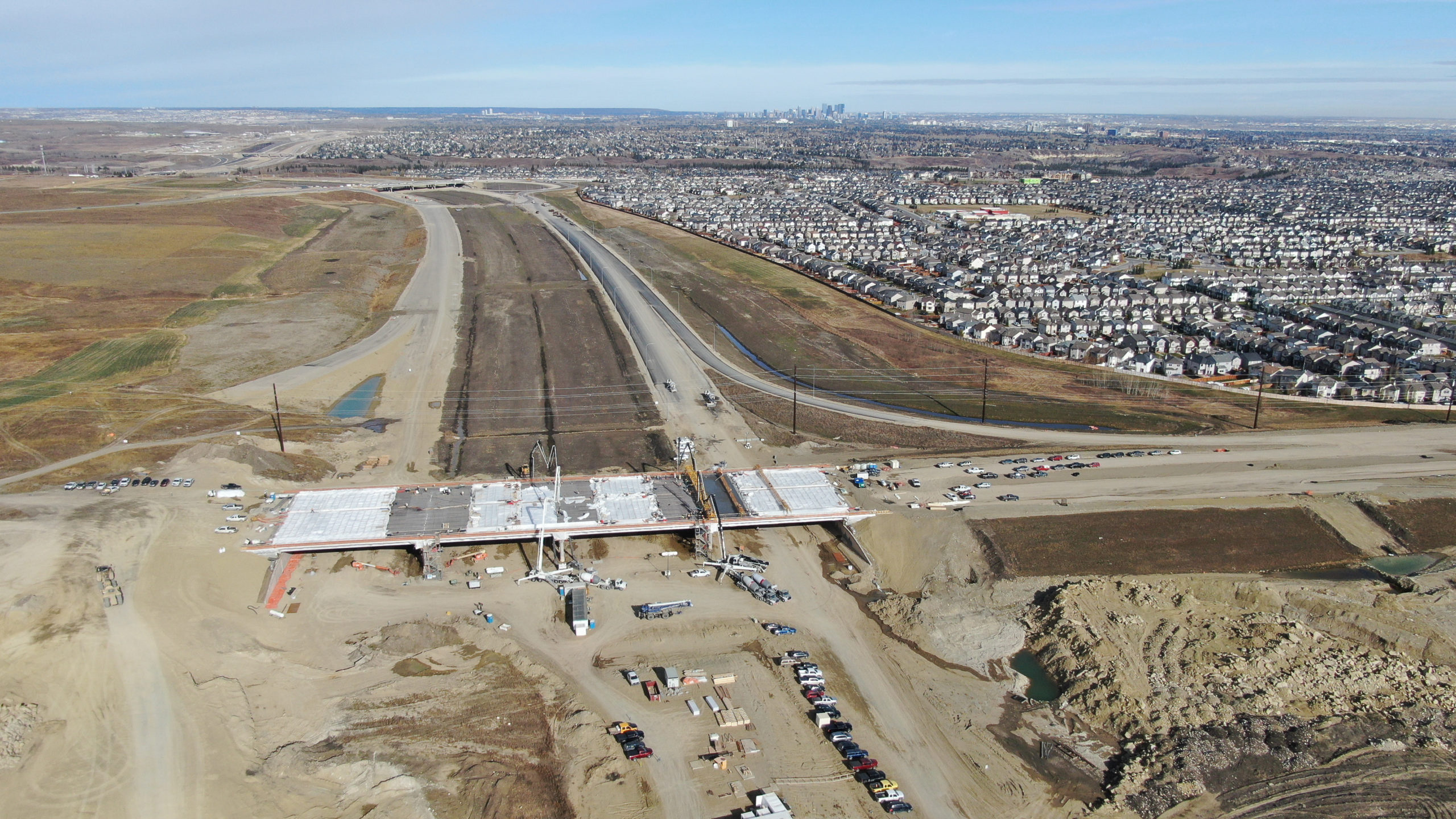 Dynamic Concrete Pumping working on the SW Calgary Ring Road project with homes in the background