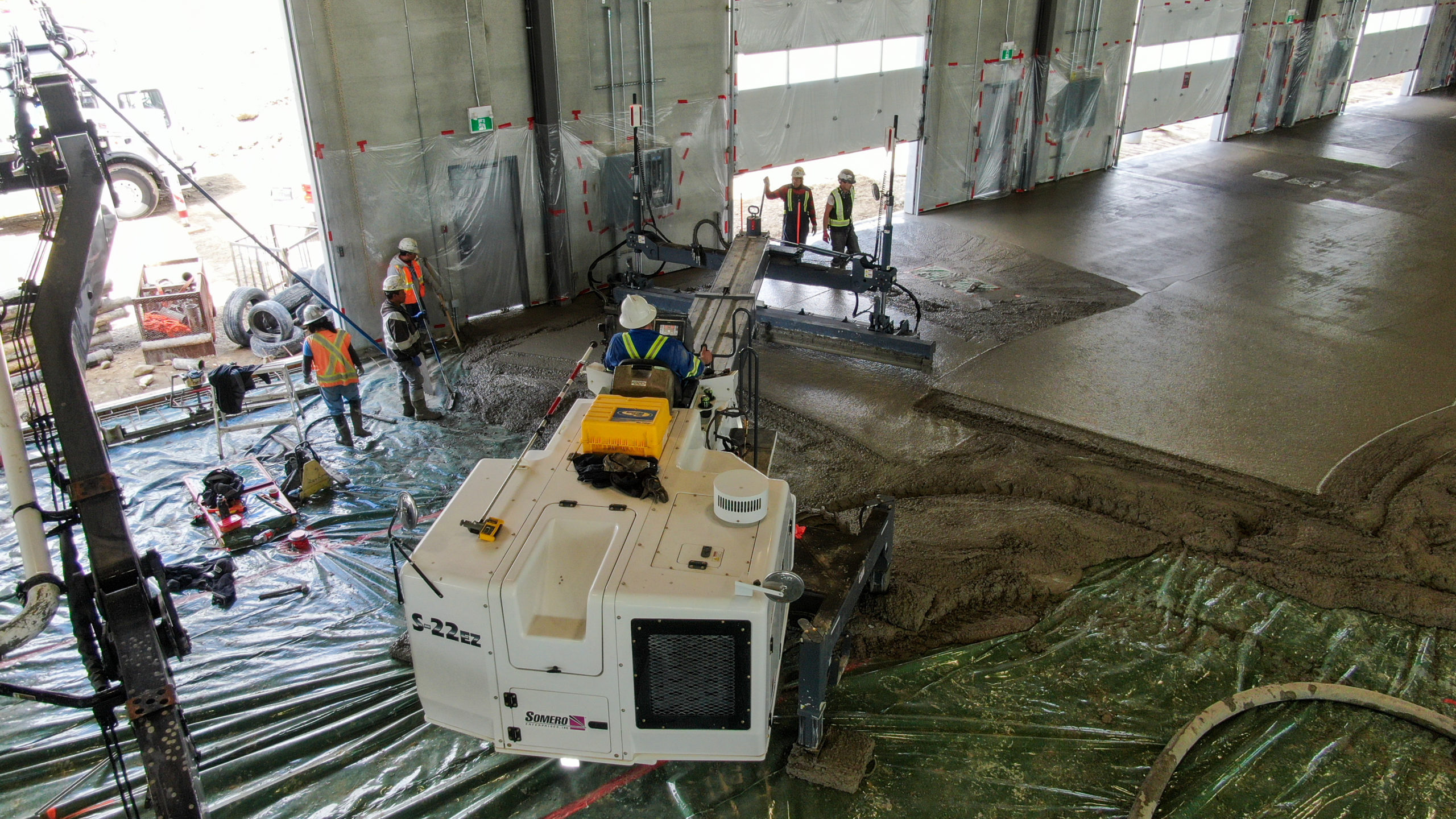 Dynamic Concrete Pumping employee using laser screed equipment on the HF11 industrial condo development project